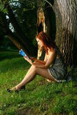 Young beautiful Woman sitting under the tree in forest — Stock Photo