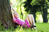 Woman sitting under tree — Stockfoto