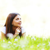 Pretty brunette girl laying on grass — Stock Photo