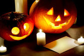 Halloween pumkins, candles and postcard — Stock Photo