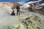Tourists in the crater of active volcano — Stock Photo