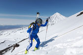 Ski mountaineering Championships: ski mountaineer climb to mountain with skis strapped to backpack — Stock Photo