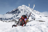 Backpack, skis and poles lie on the snow on background volcano — Stock Photo