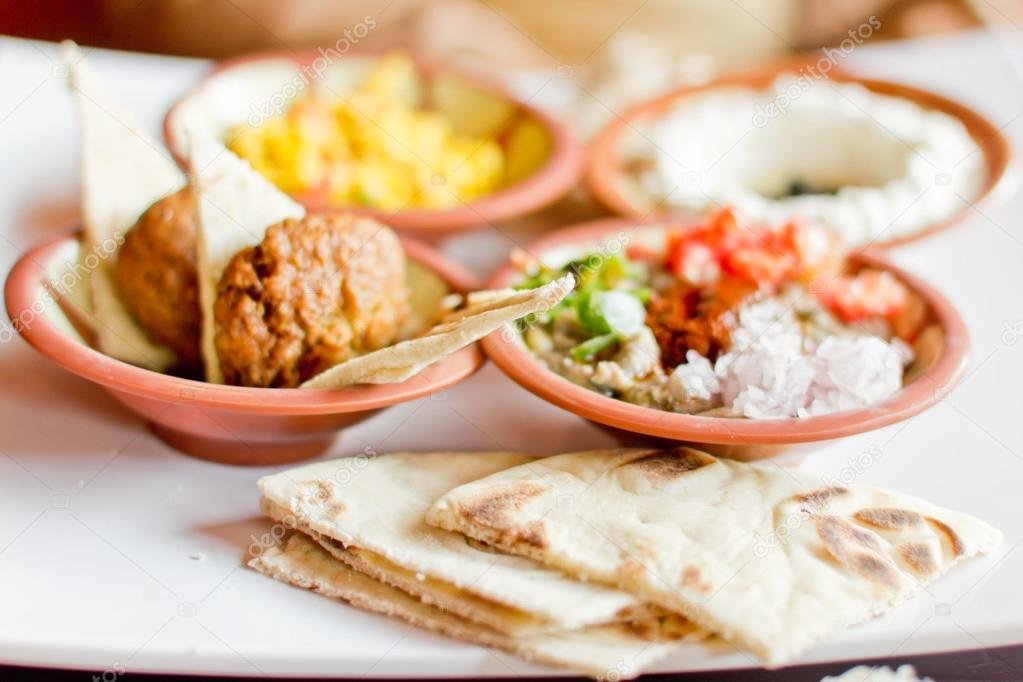 A tasty breakfast comprised of felafel with pita, eggs and vegetables — Stock Photo #12428479