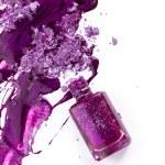 Purple nail polish and crushed eye shadow on white background — Stock Photo #27348851
