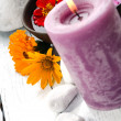 Purple candle with wildflowers — Stock Photo