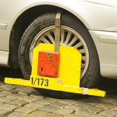 Yellow triangle wheel clamp on an illegally parked car — Stok fotoğraf
