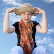 A woman in a hat on a background sky looks far — Stock Photo