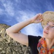 Royalty-Free Stock Photo: A woman in a hat with interest looks up at the blue sky