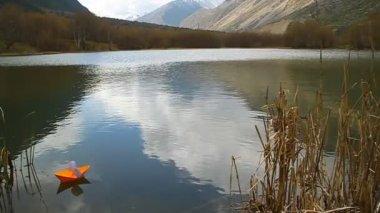 Oranžový papír člun plující v horském jezeře — Stock video