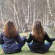 Young girls sitting on the grass and meditate — Stok fotoğraf