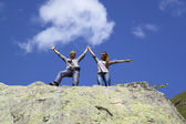 Happy mother and daughter standing on a huge rock, raising his hands up — Stock Photo