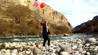 Happy woman with balloons walking on the river bank — Stock Video
