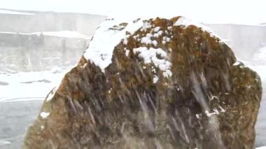 Snow falls against the backdrop of a huge flying stone, snow — Wideo stockowe