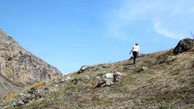A young woman climbs up the mountain and raises his arms, enjoying nature — Stock Video