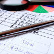 Pen placed over financial statistics and charts — Stock Photo