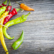 Colored hot chilli peppers on wooden textured background — Stock Photo