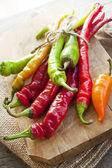 Colored hot chilli peppers on wooden chopper — Stock Photo