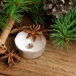 Holiday decoration with candle,fir and cinnamon on wooden backgr — Stock Photo