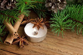 Holiday decoration with candle,fir and cinnamon on wooden backgr — Stock fotografie