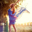 Attractive girl dancing in fluttering blue dress - Stock Photo