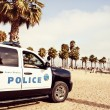 Stock Photo: Police car on the beach