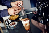 Preparation of latte macchiato with cinnamon — Stock Photo