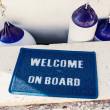 Welcome aboard mat on yacht — Stock Photo