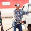 Old man filling up a car — Stock Photo