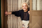 Old woman looking out of the door — Stockfoto
