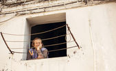 Senior woman looking through window in Bari — Stock Photo