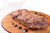 A piece of grilled meat on a wooden board — Stock Photo