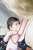 Close up portrait of baby breastfeeding — Stock Photo