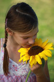 Young girl smelling a sunflower — Stock Photo