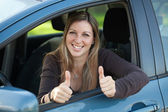 Happy female driver showing thumbs up — Stock Photo