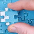 Fingers holding a puzzle piece — Stock Photo #18534331