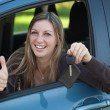Smiling woman showing a car key — Stock Photo