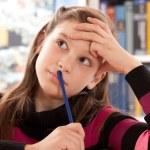 Girl thinking while doing homework — Stock Photo