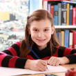 Stock Photo: Girl smiling while doing homework
