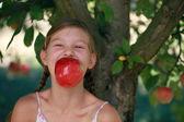 Girl biting into an apple under an apple tree — Stock Photo