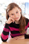 Girl thinking while sitting at a desk — Stockfoto