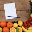 Fruits on wooden board with notebook — Stockfoto #25081045