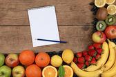 Frutas em uma placa de madeira com notebook — Foto Stock