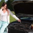 Young woman at a broken down car — Stock Photo