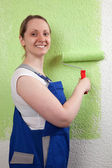 Young woman painting a wall — Stock Photo