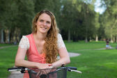 Young woman leaning against a bike — Stock Photo