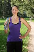 Sportliche junge frau mit wasserflasche — Stockfoto