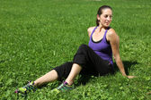 Sporty woman takes a break on a meadow after running — Stock Photo