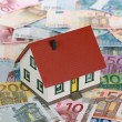 Bank financing a real estate with a house on banknotes — Stock Photo