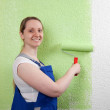 Smiling woman painting with paint roller — Stock Photo